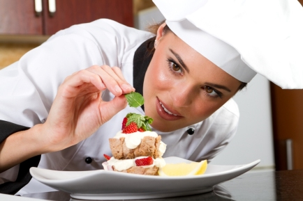 beautiful professional female chef decorating dessert
