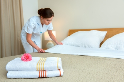 Hotel room service. Young maid changing bedclothes in a room