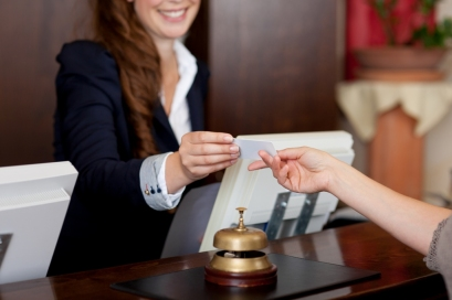 smiling female receptionist passing card to guest