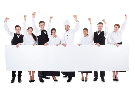 Cheerful excited catering staff showing banner. Isolated on white