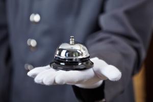 Hand eines Portiers mit einer Hotelglocke